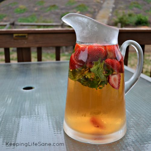 pitcher of iced tea with strawberries and mint sitting on an outside table
