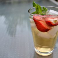 glass of ice tea with ice cubes, strawberries and mint leaves