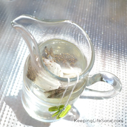 Glass pitcher sitting outside in the sun with tea bags