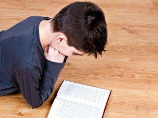 boy lying on hardwood floor and reading a book