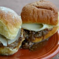 two slider roast beef sandwiches on dark red plate with meat adnd cheese and gravy dripping out.