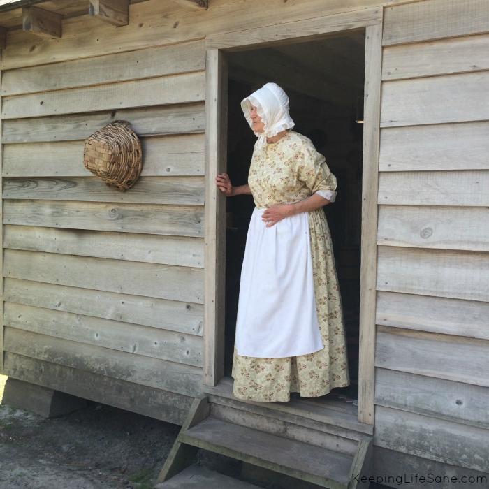 Lady wearing 1800's dress in doorway of wood house
