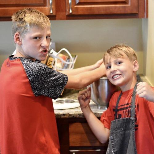 2 boys baking, both wearing red shirts