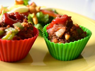 yellow plate with red and green muffin liner with meatloaf and side salad