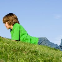 boy laying on grass in jeans and green shirt reading a book