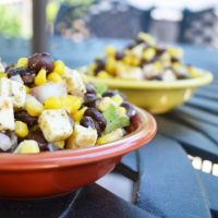 Mexican Corn and Bean Salad is a red and yellow bowl on outside iron table