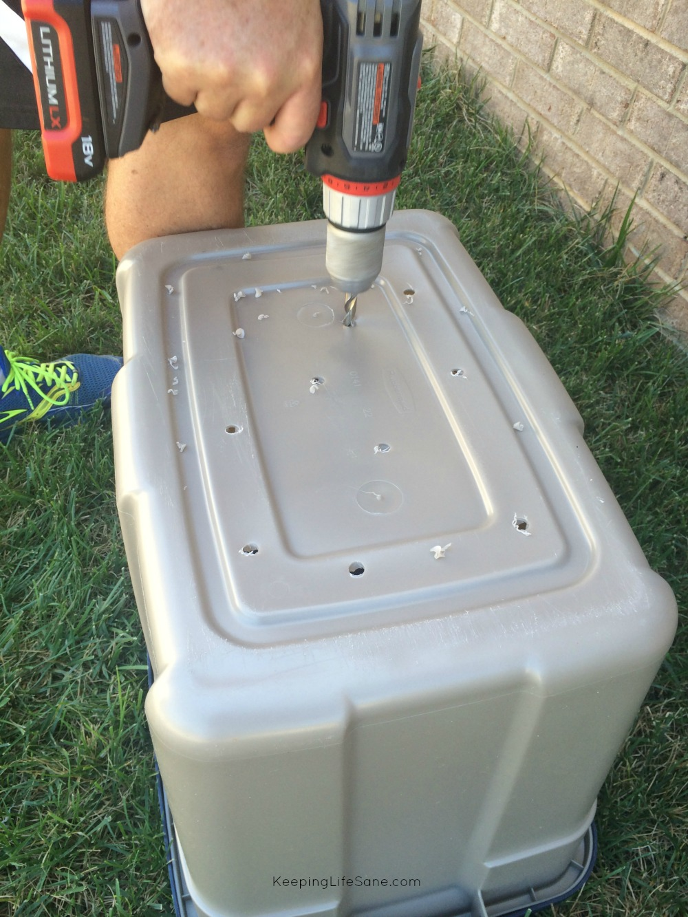 Plastic Rubbermaid bin that's upside down in grass with a man's hand drilling holes in the bottom.