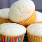 stack of three vanilla cupcakes with colorful cupcake liners