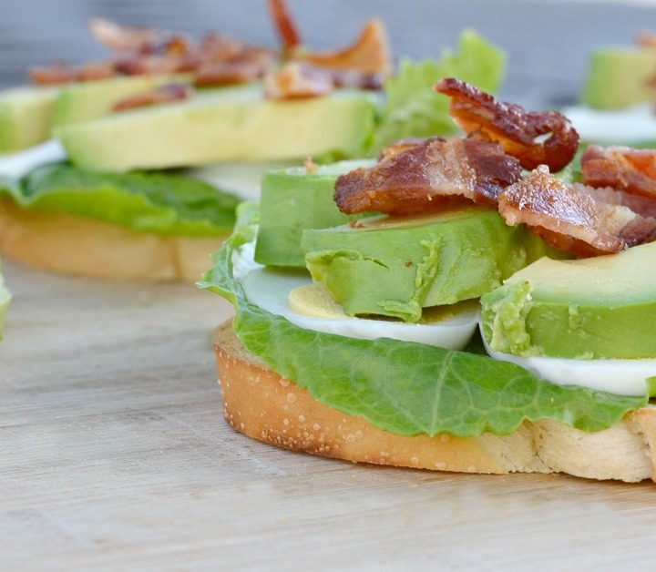 toast with lettuce, hard boil eggs, gree avocados with bacon on top