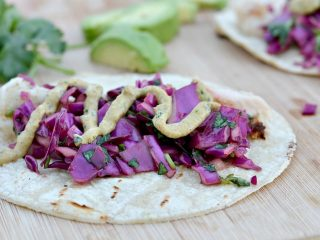 fish tacos on tortilla with red cabbage and cilantro and avocados