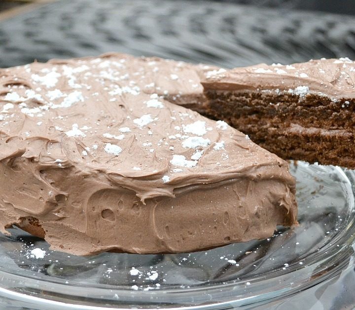 Round Chocolate cake with slice being taken out of it