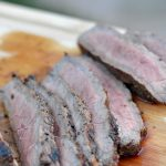 uicy london broil sliced up on a cutting board