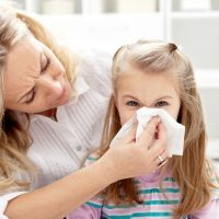girl with long hair with mom holding a tissue so she can blow her nose