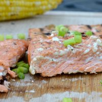 salmon cutting board with green chives on top