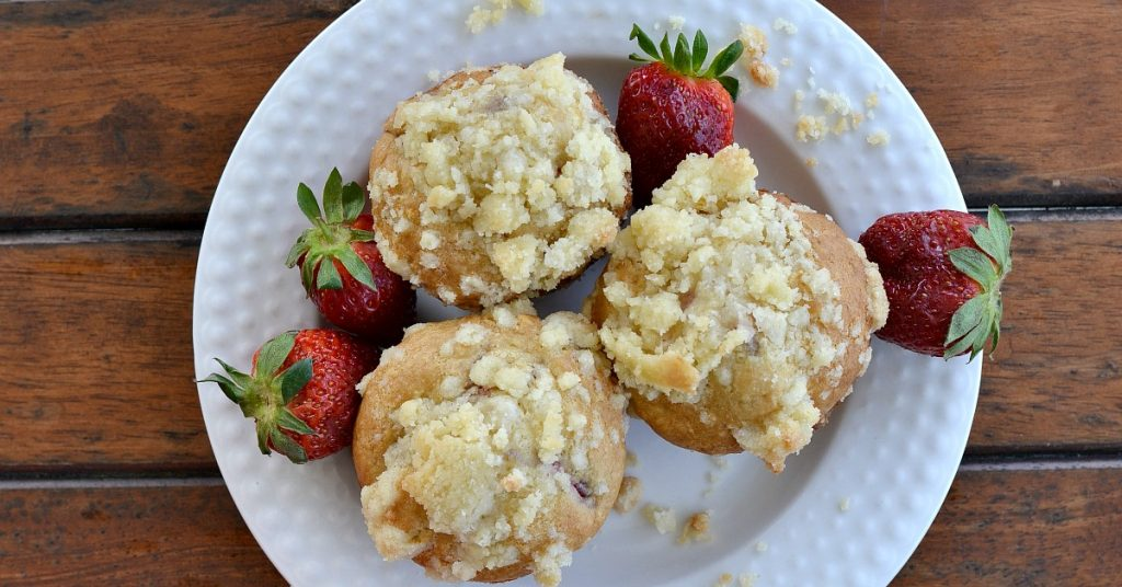 overhead view of white plate with three strawberry muffins with real red strawberry off to the sides