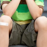 kid sitting on step with bandaid on knew