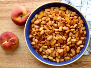 overhead view of peach baked beans in blue bowl on cutting board
