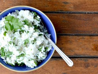overhead view of cilantro lime rice on blue bowl with spoon