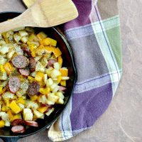 Overhead view of potatoes, sausage, pepper and onion in cast iron skillet with a wooden spoon