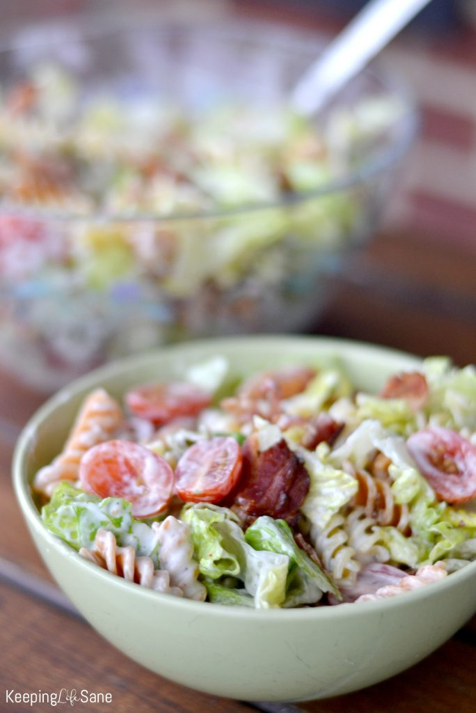 light green bowl with creamy pasta salad with larger clear bowl in background