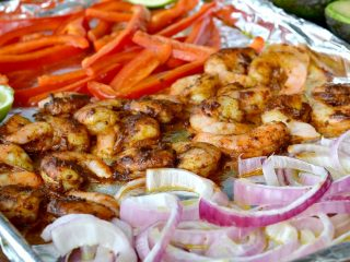 Closeup view of cooked shrimp, onions, red peppers and lime on foil line baking sheet