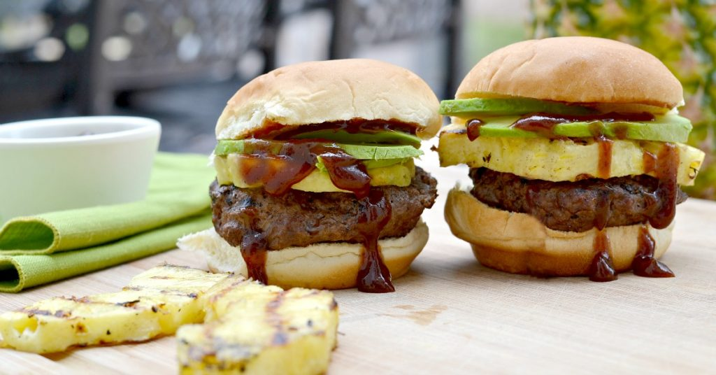 two grilled sliders with pineapple avocado and lots of dripping barbecue sauce