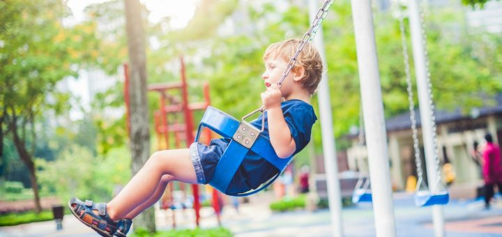 little boy with blond hair swinging at playground in a toddler swing