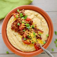 Overhead view of bowl with cheese grits topped with bacon, tomatoes and green onions