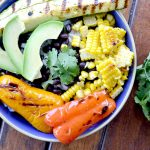 overhead view of burrito bowl with grilled corn, avocados, peppers, with cilantro, black beans and sliced avocado