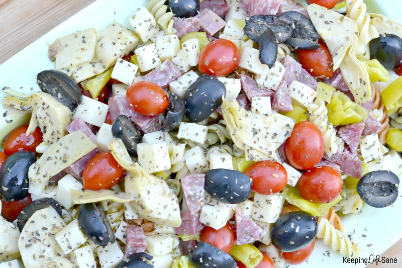 overhead closeup view of antipasto with rotini, grape tomatoes, olives, cheese cubes, artichokes, salami and cheese cubes