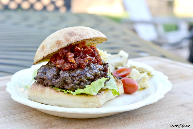 white platter with burger with lettuce and sun dried tomatoes.