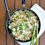 Overhead view of wok with vegetable fried rice with green onions laying on the side of the pot