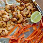 overhead and closeup view of cooked shrimp, red peppers and lime on foil line baking sheet