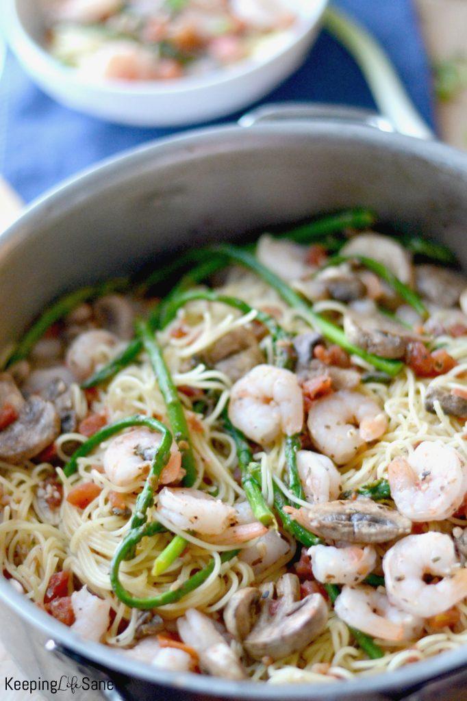 big silver pot with pasta, shirmp and asparagus