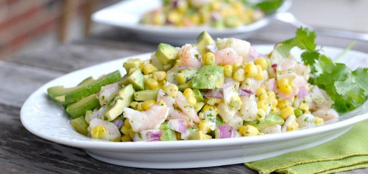shrimp avocado salad with corn on white plate with cilantro garnish