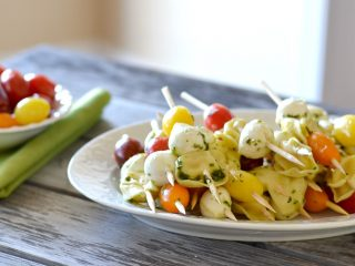 white platter with a bunch of tomatoes, mozzarella and tortellini skewers.