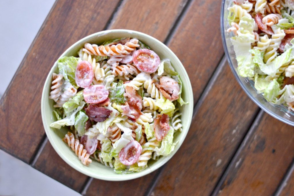 overhead view of pasta salad on brown table