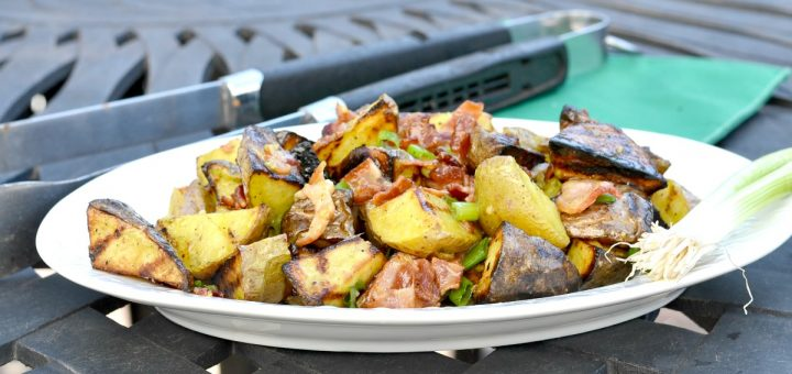 White plate with grilled potato salad sitting on black outside table with grilling tongs and green napkin