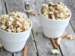 two white popcorn bowl with cinnamon popcorn overflowing