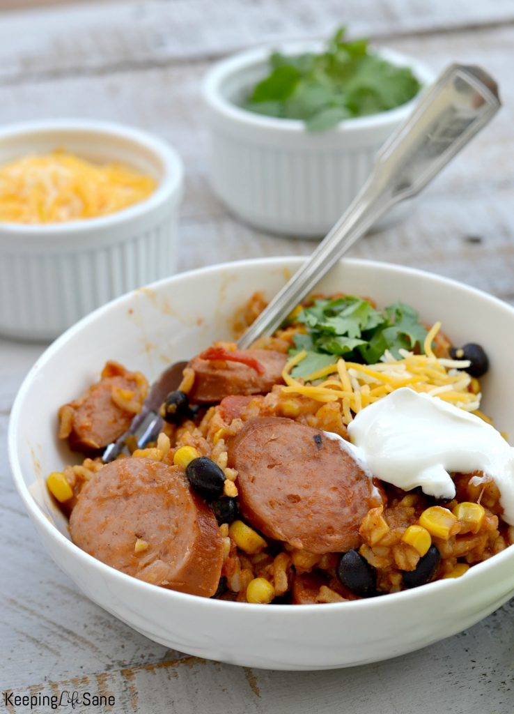 Mexican sausage recipe in white bowl toppings in background