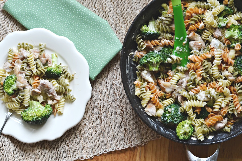 overhead view of skillet with pasta, broccoli and chicken meal with small white plate with and green napkin