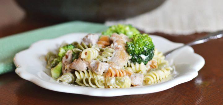 small white plate with tricolored rotini pasta, broccoli and chicken