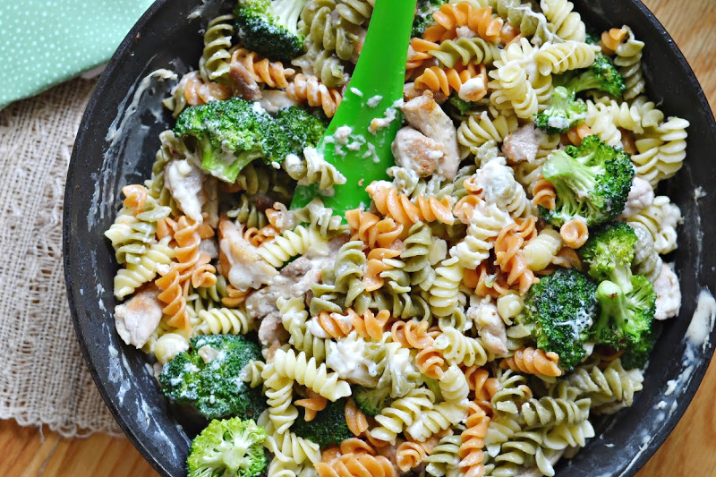 closeup overhead view of skillet with pasta, broccoli and chicken meal