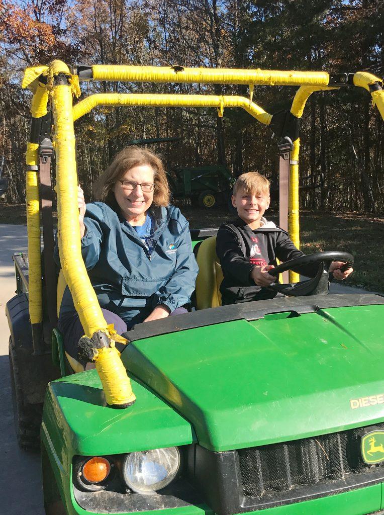 grandma and child sitting in green gator ATV
