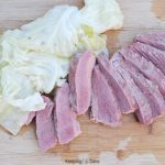 sliced corn beef on a cutting board with cabbage
