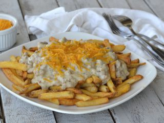 southern poutine on white plate on grey wooden table, french fries, suasage gravy and shredded chedder cheese