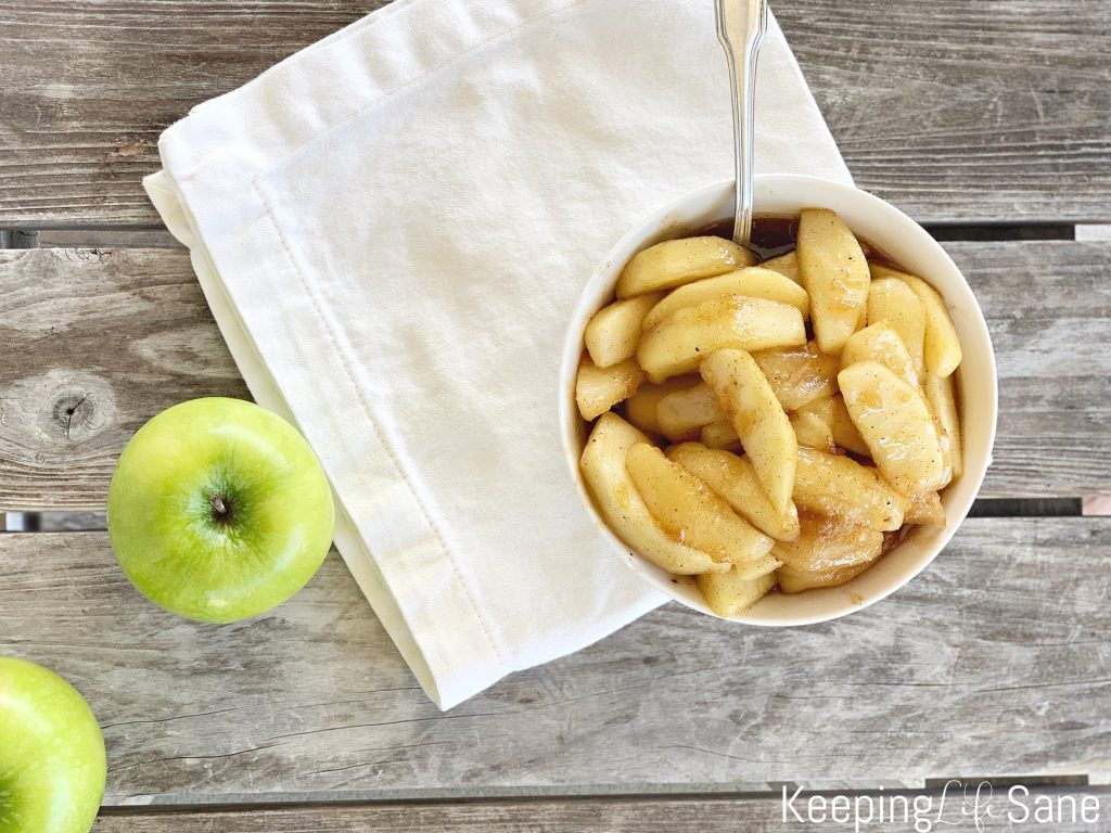bowl of fried apples from overhead view on a white napkin with a green apple