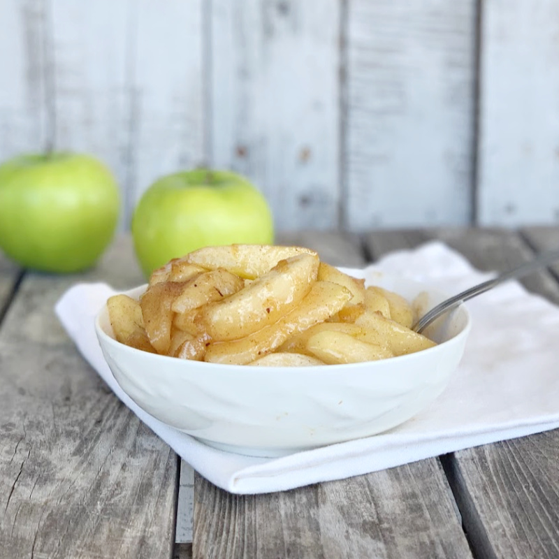 bowl of fried apples on a white napkin with a green apple