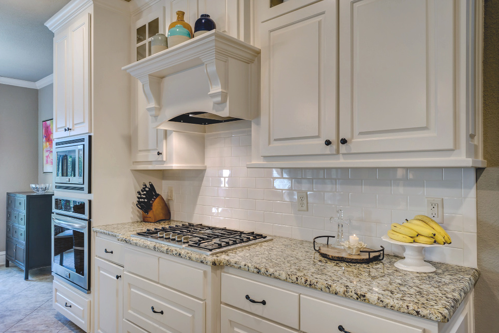 Clean kitchen with white cabinets with bananas on a white cake plate