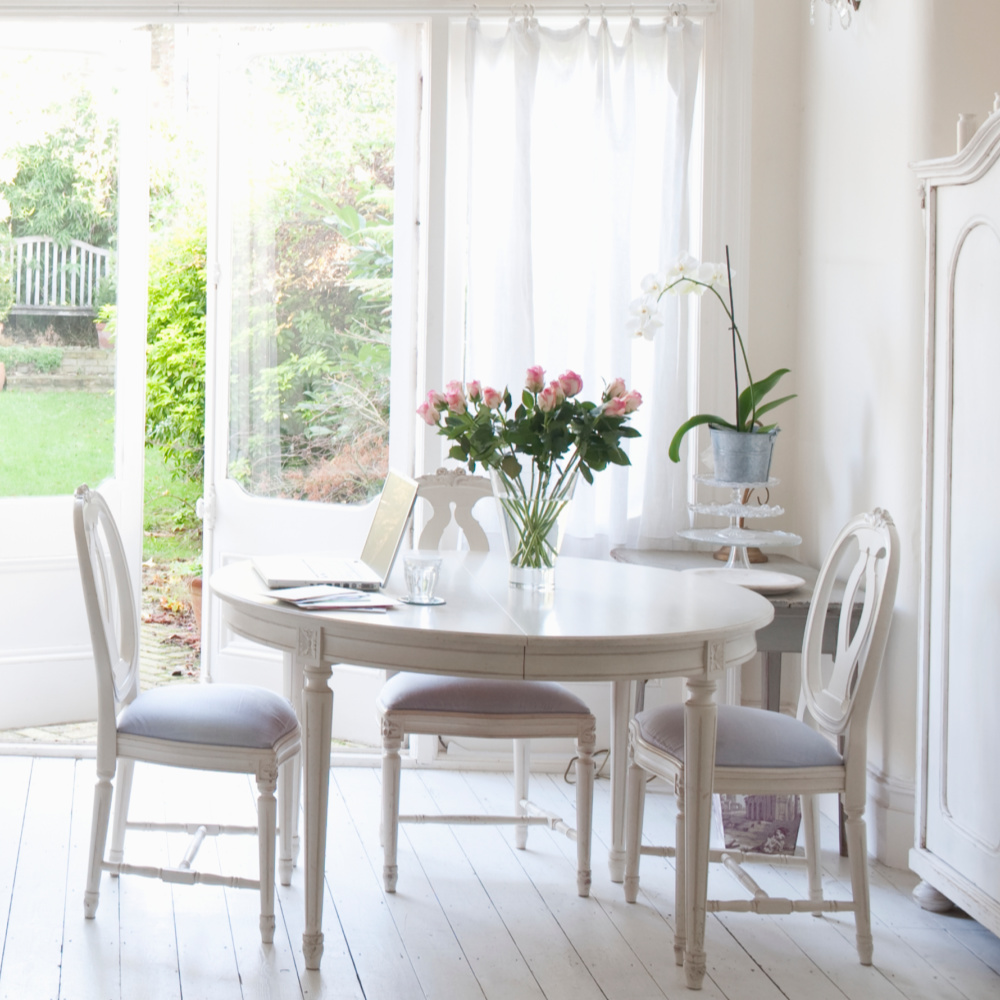 white round kitchen table near doors with white curtains that open with flower on table